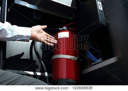 Car fire extinguisher. The bus driver checks the fire extinguisher.