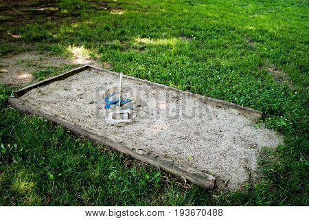 Old horseshoe pit with sand out in the backyard
