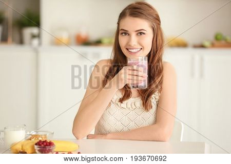 Weight loss concept. Beautiful young woman drinking healthy delicious smoothie in kitchen