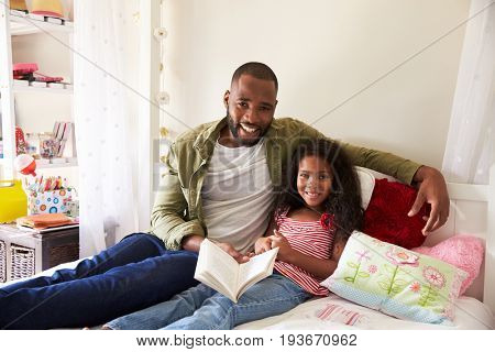 Portrait Of Father And Daughter Siting On Bed Reading Book