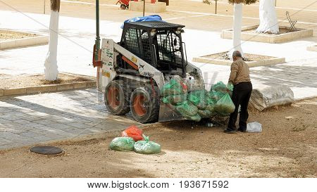 Jerusalem, Israel - May 21, 2017: Street sweeper senior man takes garbage bags and puts it in cleaning sweeper vehicle. Jerusalem municipality employs arab workers to clean the city streets.
