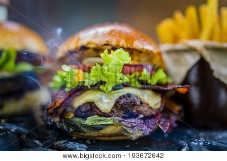 Tasty smoked and grilled beef burger with lettuce, cheese and bacon served with french fries on wooden table with copyspace, smoke mesquite timber wood in background.