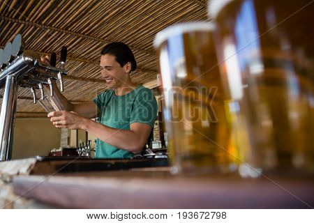 Close-up of beer glasses on counter with bartender working at restaurant
