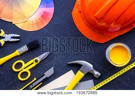 Reparing home concept. Paint and tools on black stone desk background top view.