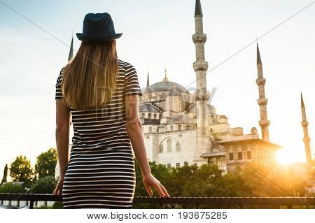A young tourist girl with a beautiful figure looks from the hotel terrace to the world famous blue mosque Sultanahmet in Istanbul, Turkey. Travel, sightseeing, relaxation.