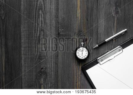 Stopwatch, pen and pad on wooden background top view copyspace.
