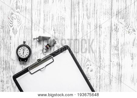 To judge competition. Stopwatch, whistle, pad on wooden table background top view copyspace mockup.