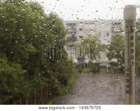 rain drops on glass street views green trees the heat the thermometer