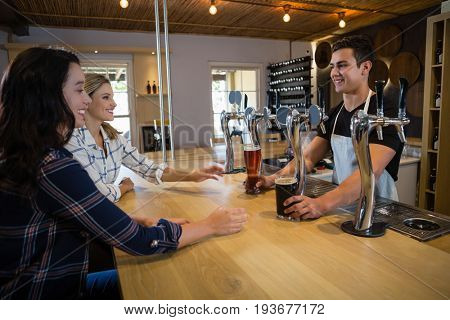 Bartender serving drinks to smiling female friends at counter in restaurant