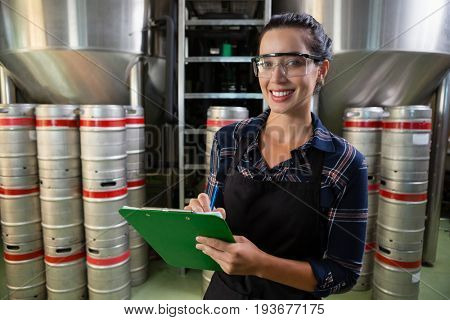 Portrait of smiling female worker holding clipboard by storage tanks at brewery