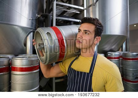 Worker looking away while carrying keg by storage tanks at brewery