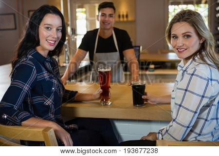 Portrait of smiling beautiful friends with drinks and bartender at restaurant