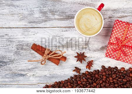 Cup of coffee, wooden background. Cinnamon and gift box. Be grateful with coffee.