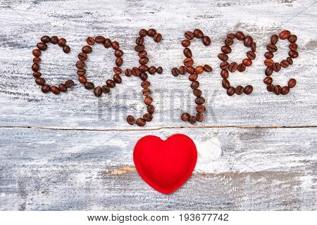 Word coffee from grain. Fabric heart on wooden background. With love for gourmet.