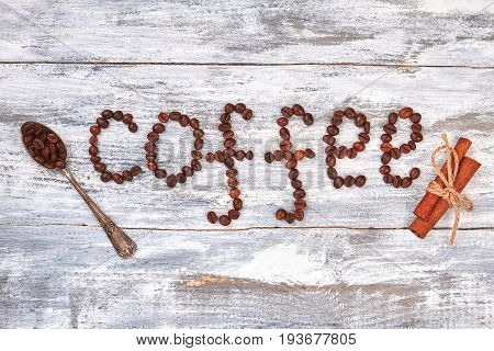 Coffee, retro spoon, cinnamon. Coffee beans on wooden background. Energy for creativity.