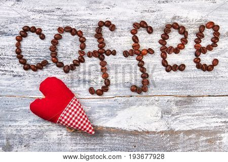 Coffee grain and handmade product. Red heart on wooden background.