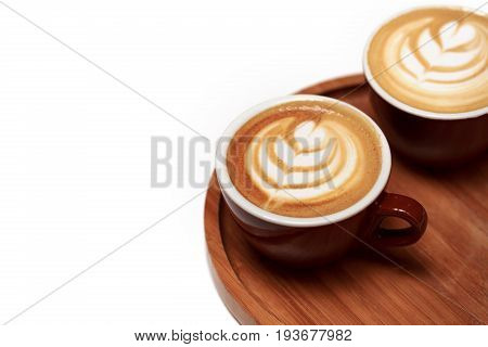 Two brown cups of cappuccino with latte art on wooden board and on white table. Top view, place for text.