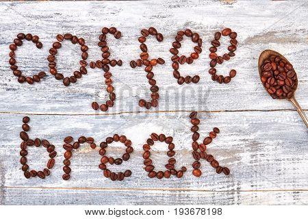 Phrase coffee break from beans. Grain and old spoon on wooden background.