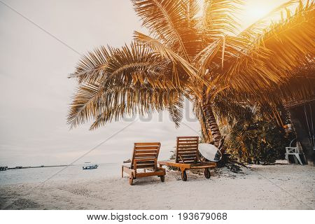 Stunning sunset on Maldives island: rear view of two deck chairs looking on Indian ocean and covered by palm black reflective surfboard sand beach empty speedboat copy space zone for text or logo