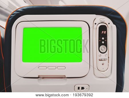 Empty mock-up of aircraft multimedia screen with remote control close-up view of blank placeholder of airplane monitor filled with solid green behind passenger seat with multiple buttons and sockets