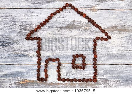Coffee building on wooden background. House from coffee beans. Coffee and creative.