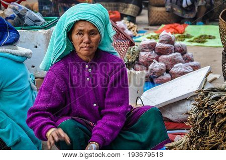 MUANG SING, LAOS - DECEMBER 28, 2012: Women selling vegetables in the morning market in the village of Muang Sing Laos