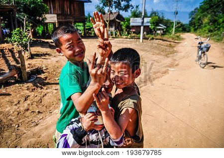 MUANG SING, LAOS - DECEMBER 28, 2012: Local boys in a small ethnic community near the village of Muang Sing in Laos