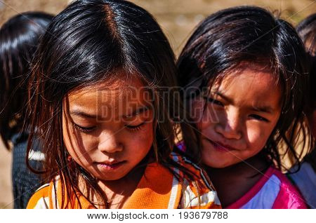 MUANG SING, LAOS - DECEMBER 28, 2012: Local girls in a small ethnic community near the village of Muang Sing in Laos