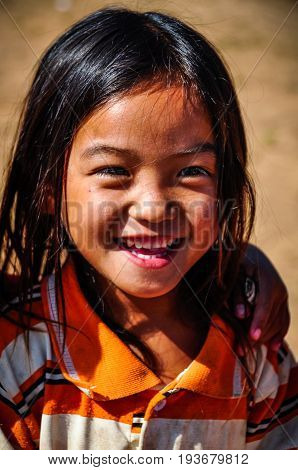 MUANG SING, LAOS - DECEMBER 28, 2012: Local girl in a small ethnic community near the village of Muang Sing in Laos