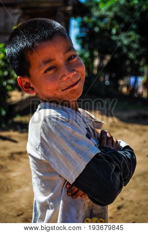 MUANG SING, LAOS - DECEMBER 28, 2012: Local boy in a small ethnic community near the village of Muang Sing in Laos