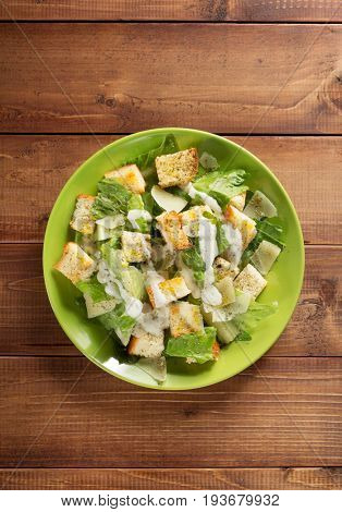 caesar salad in plate at wooden  background