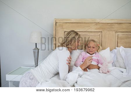 Mother checking sick daughter temperature with digital thermometer in the bedroom at home