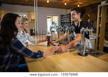 Bartender serving drinks to female friends at counter in restaurant