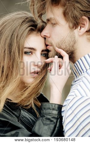 Young couple of sensual lovers outdoors. Sexy woman and cute girl with stylish makeup and long hair and handsome caucasian man touching each other with love and tenderness