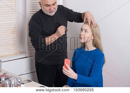 Man applying powder on girl face skin with makeup brush. Woman pretty fashion model with long blond hair and smartphone or mobile phone in beauty salon. Visage. Weblog blogging