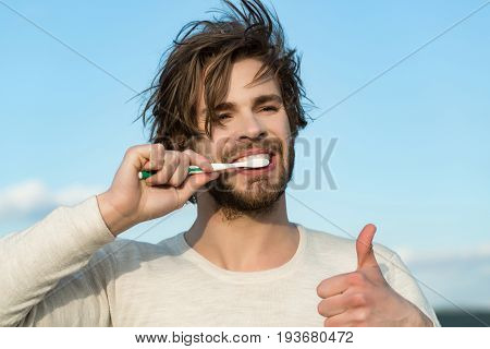 thumb up of happy handsome man brush teeth with toothpaste has beard and hair in underwear on blue sky background morning outdoor hygiene and spa metrosexual