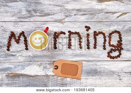 Cup of cappucino, wooden background. Paper card, coffee beans decoration.