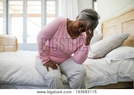 Tense senior woman sitting on bed in bedroom at home