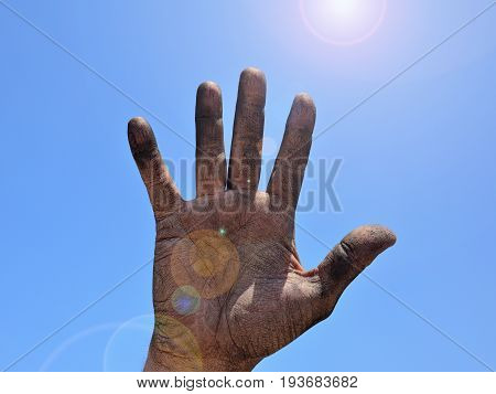 Open right man's hand smeared with black soot against the blue clear sky