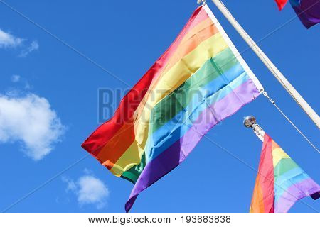A rainbow multicolor flag The symbol LGBT is fluttering in the wind against the background of a blue bright sunny sky. freedom. tolerance. Lesbian couples. peace. love.