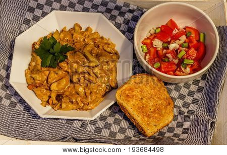 Mushroom stew with parsley, tomato salad and bread