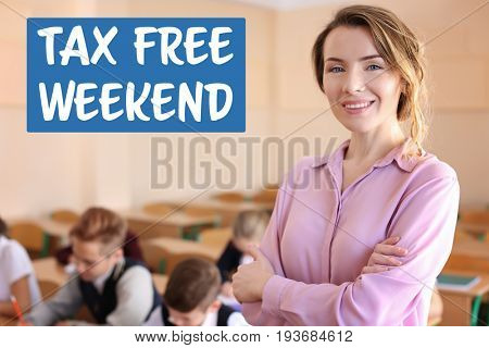 Teacher in classroom at school. Text TAX FREE WEEKEND on background