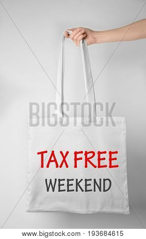 Woman holding textile shopping bag with text TAX FREE WEEKEND on light background