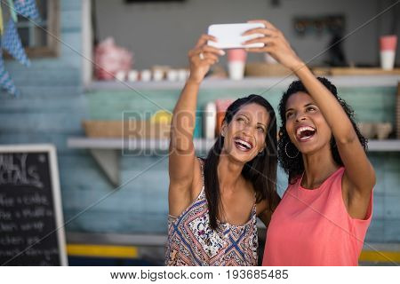 Happy friends taking selfie from mobile phone