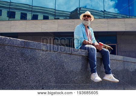 Smiling bearded man surrounded by skyscrapers, sitting, having cheerful appearance holding cup, mid shot