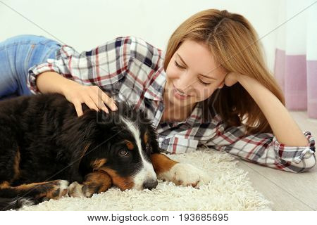 Young woman with cute funny dog lying on floor at home
