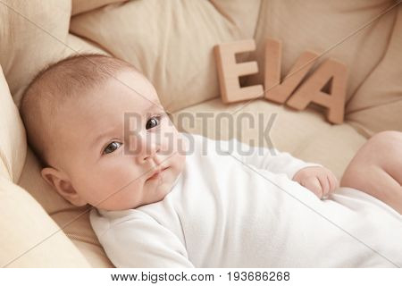 Cute baby with word EVA lying in armchair. Choosing name concept