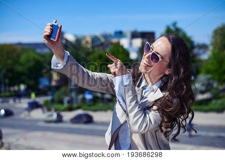 Mid shot of wonderful lady taking selfie in front of city panorama