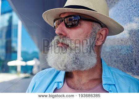 Portrait of stylish elderly man wearing sunglasses looking far, thinking and enjoying free time, close-up shot