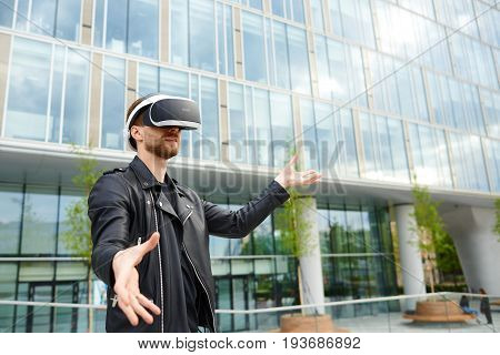 Amazed young Caucasian male in black clothing experiencing virtual reality using oculus rift headset for entertaining himself gesturing as if touching something while playing video game in cityscape